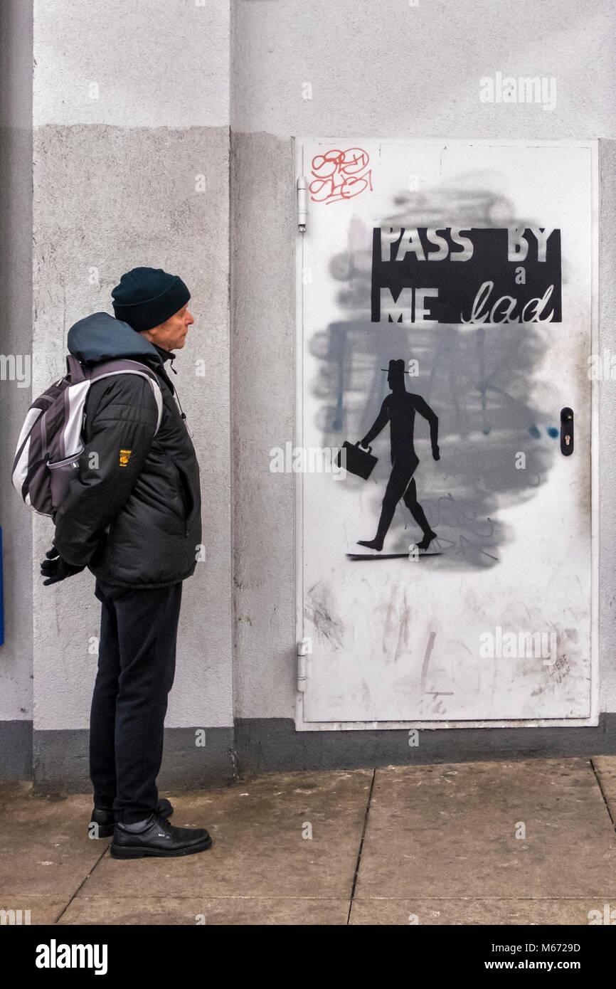 Berlin, Mitte, Alexanderplatz.  Senior elderly man with rucksack looks at street art - Silhouette of man with brief - Stock Image