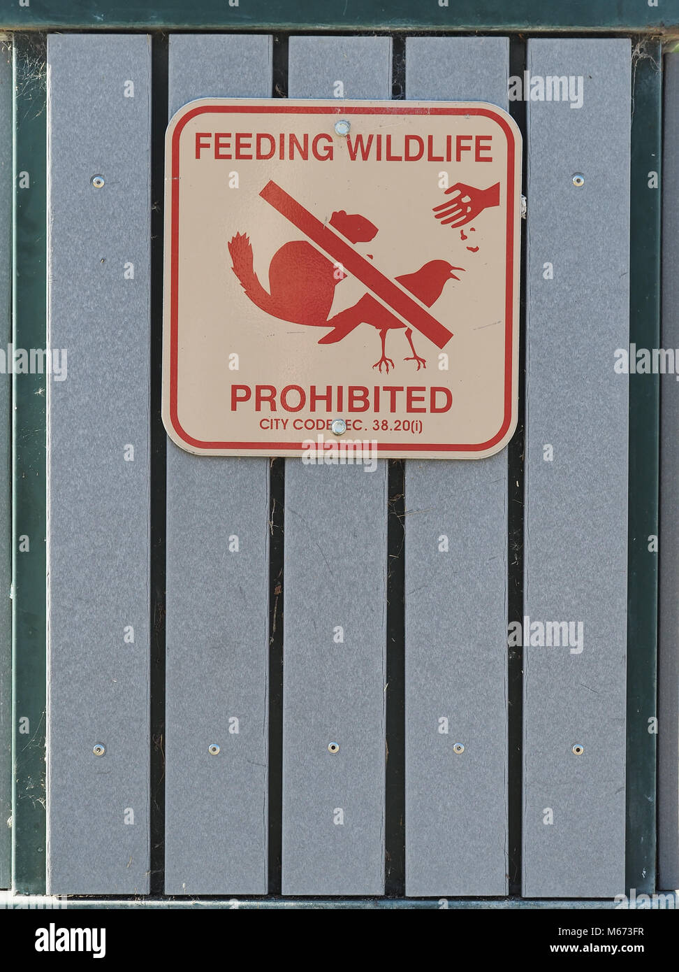 'Feeding wildlife prohibited' sign on a trash can in a park in San Francisco, California - Stock Image