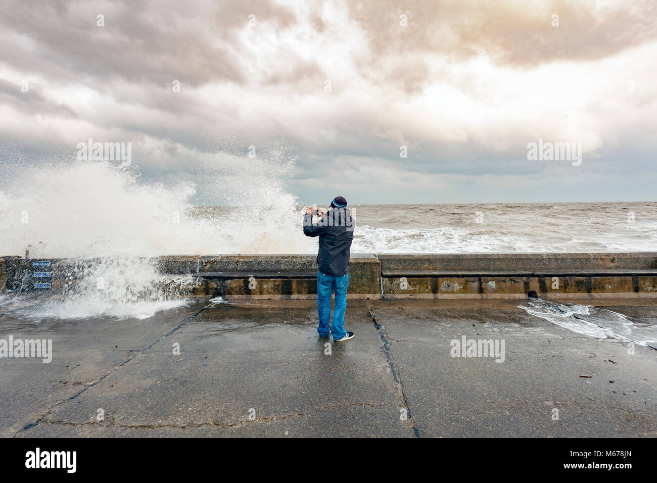 A man taking pictures of the crashing waves on the promenade wall at Colwyn Bay, Wales as a result of the Beast - Stock Image