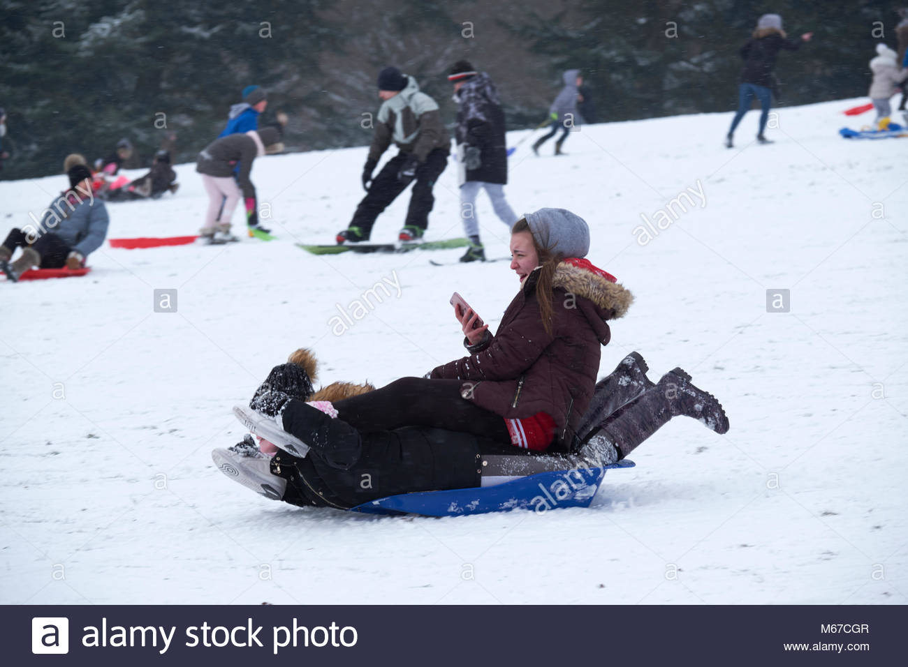 Nottingham, England, 1 March 2018 Two girls with mobilephone on same sledge.Sledging in front of Wollaton Hall in - Stock Image