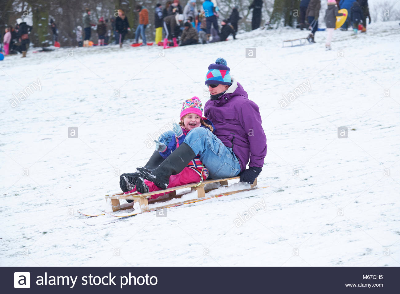Nottingham, England, 1 March 2018 FGather and young daughter sledging in front of Wollaton Hall in snow from 'The - Stock Image