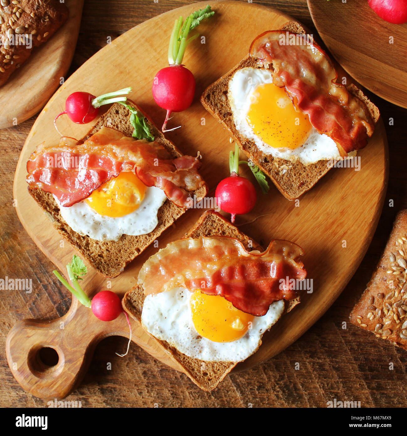 Breakfast , crispy bacon, fried eggs and bread. Sandwiches on cutting board. Rustic table . Top view - Stock Image