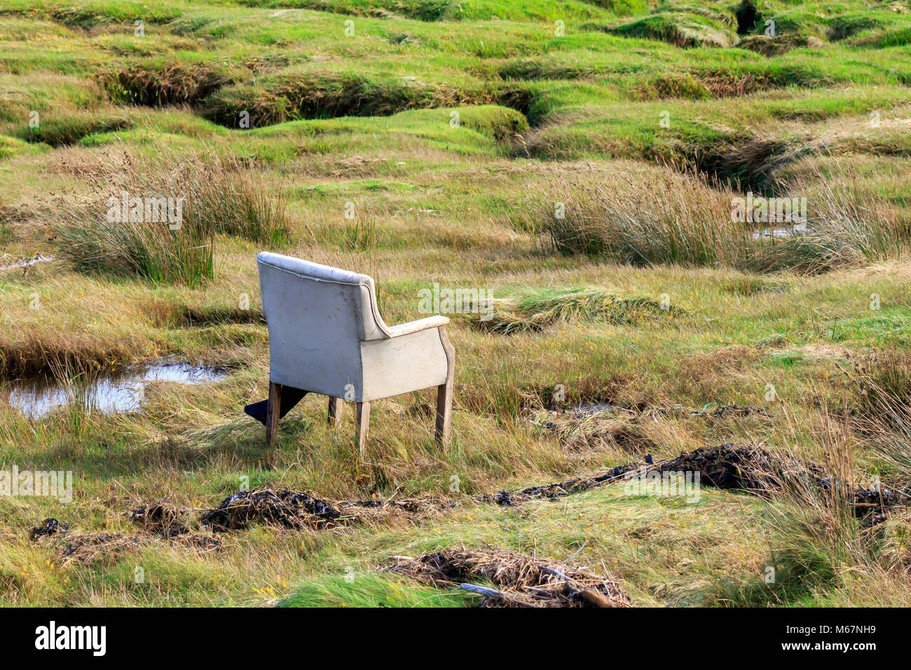 Old discarded armchair on the banks of the Solway Firth Scotland - Stock Image