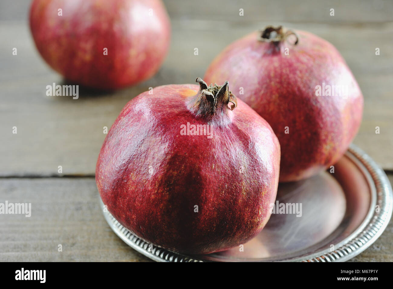Red juicy fruit pomegranate in a tray - Stock Image