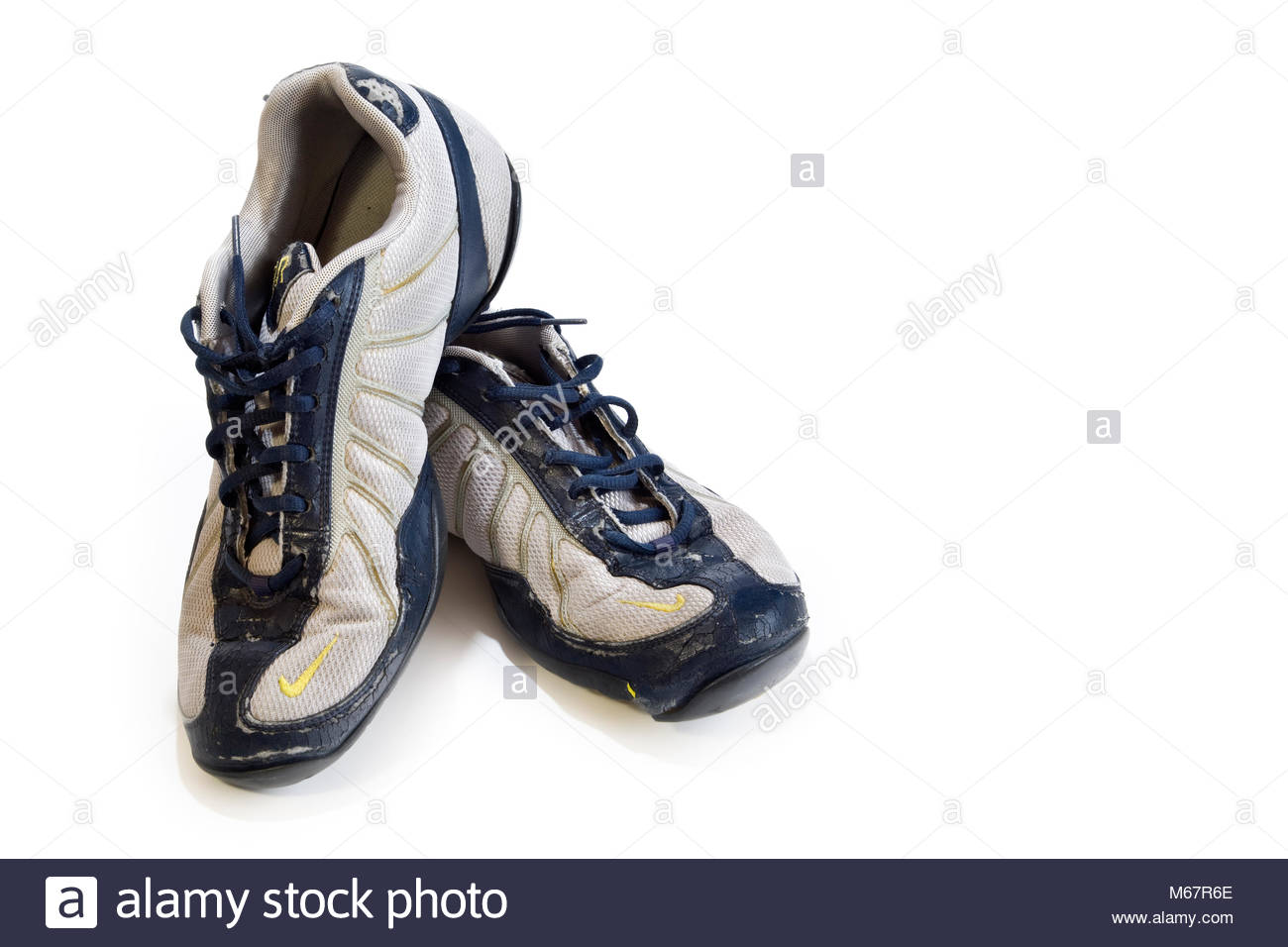 Close-up of pair of worn out trainers, isolated on white with copy space - Stock Image
