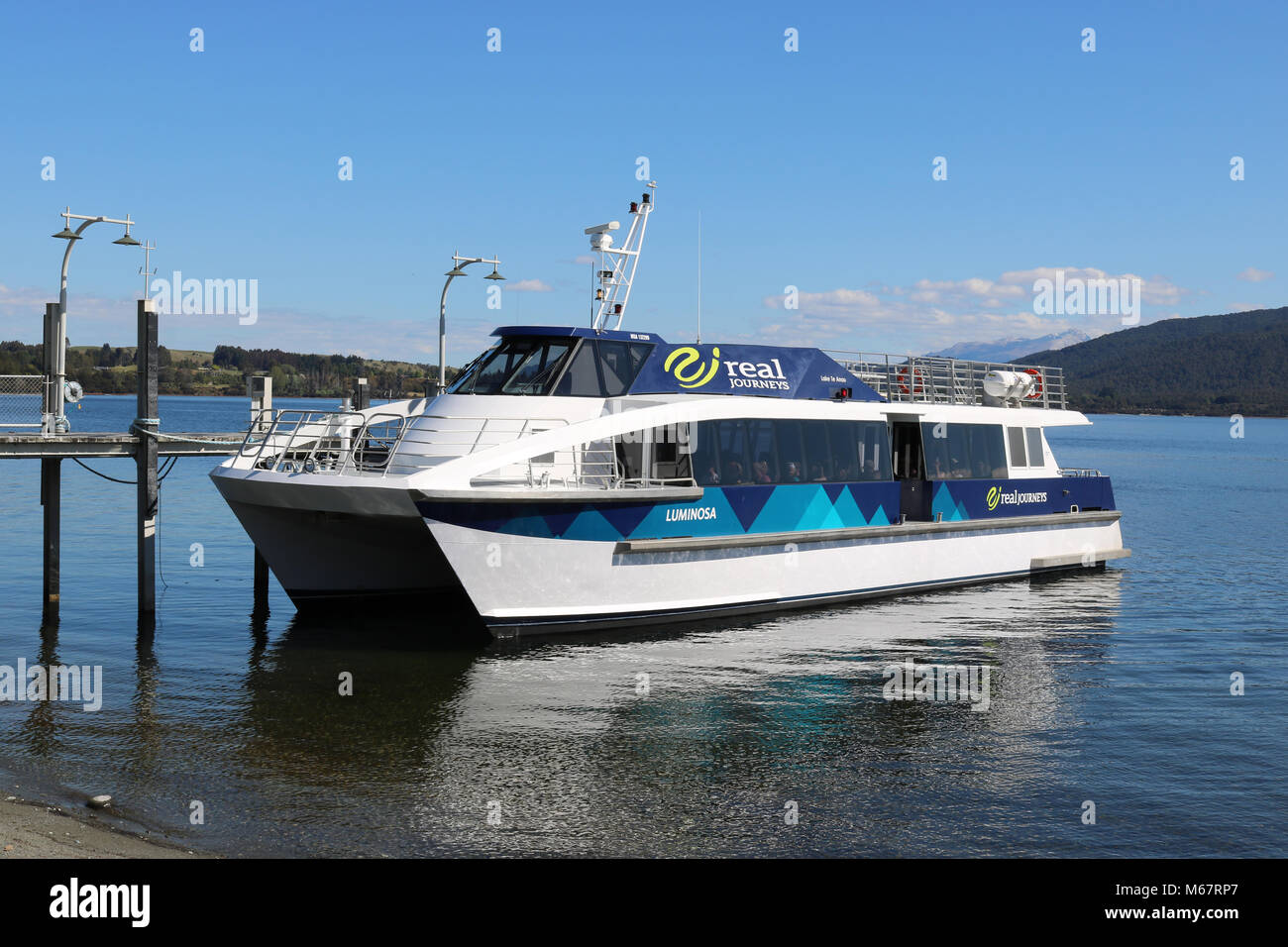 Catamaran cruise boat Luminosa operated by Real Journeys for cruises on lake Te Anau in Fiordland, South Island, - Stock Image
