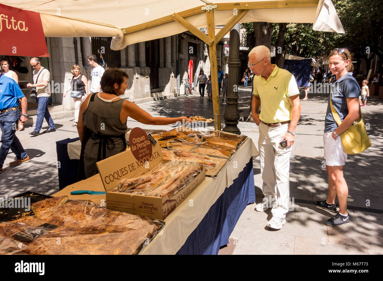 Vendor of artisan bakery stall offering pieces of bread sample for tasting to customers, Rambla de la Llibertat, - Stock Image