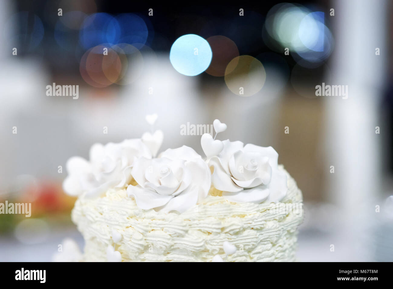 White wedding cake detail - marzipan decorative flowers and hearts - Stock Image