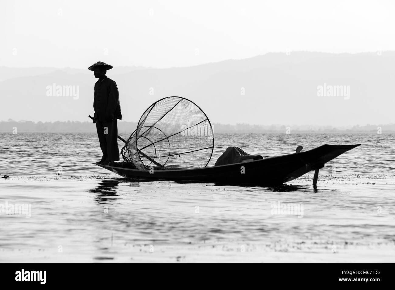 Intha leg rowing fishermen at Inle Lake, Shan State, Myanmar (Burma), Asia in February - fisherman stood on boat - Stock Image