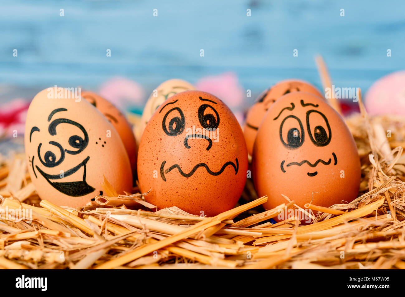 Closeup Of Some Brown Different Eggs With Funny Faces On A Pile Straw