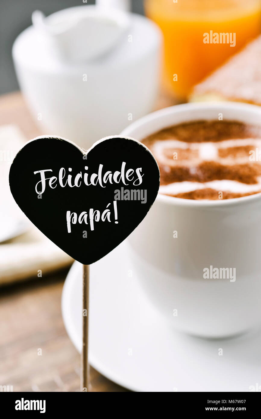 a heart-shaped signboard with the text felicidades papa, congratulations daddy written in spanish, and a cup of - Stock Image