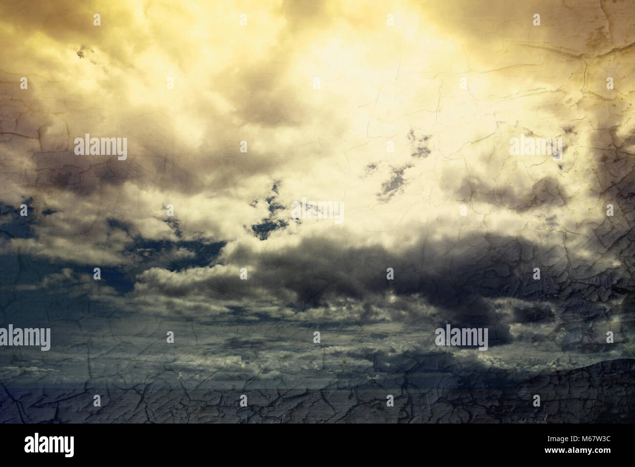 Global warming concept landscape. Dramatic cloudy sky and dry cracked earth - Stock Image