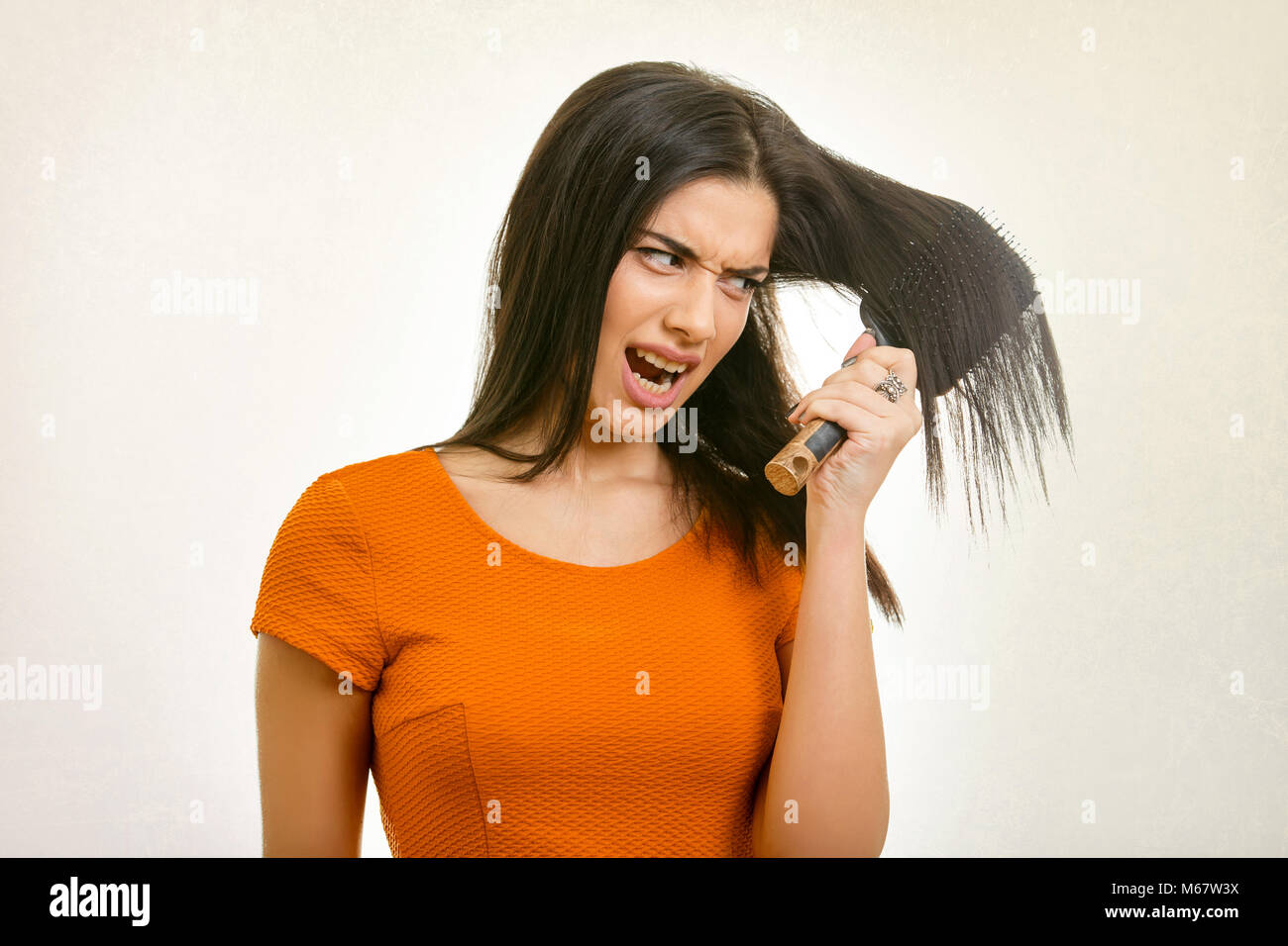 Woman with tangled hair stuck in comb - Stock Image