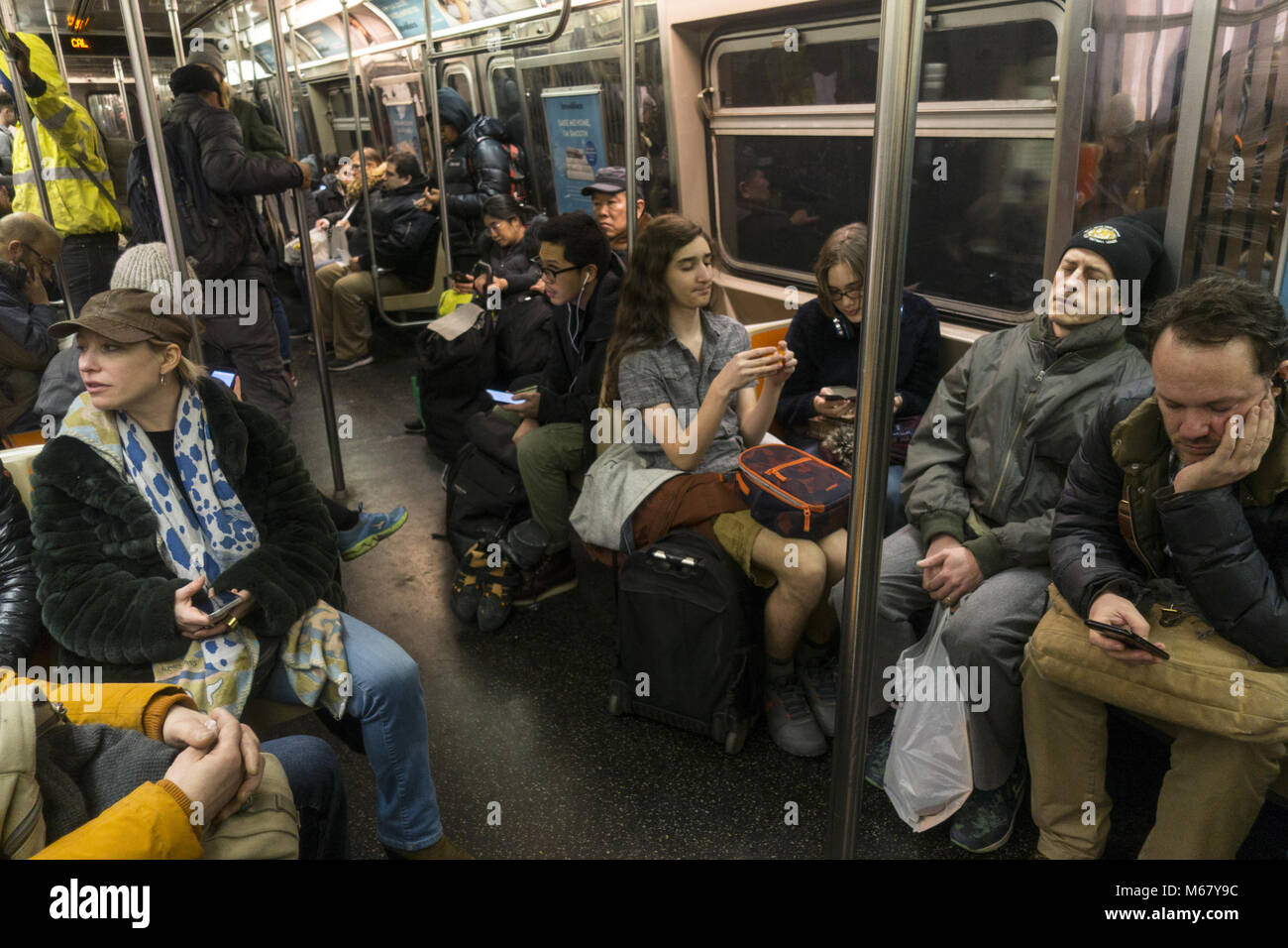 People ride a subway train in Brooklyn New York in the ...