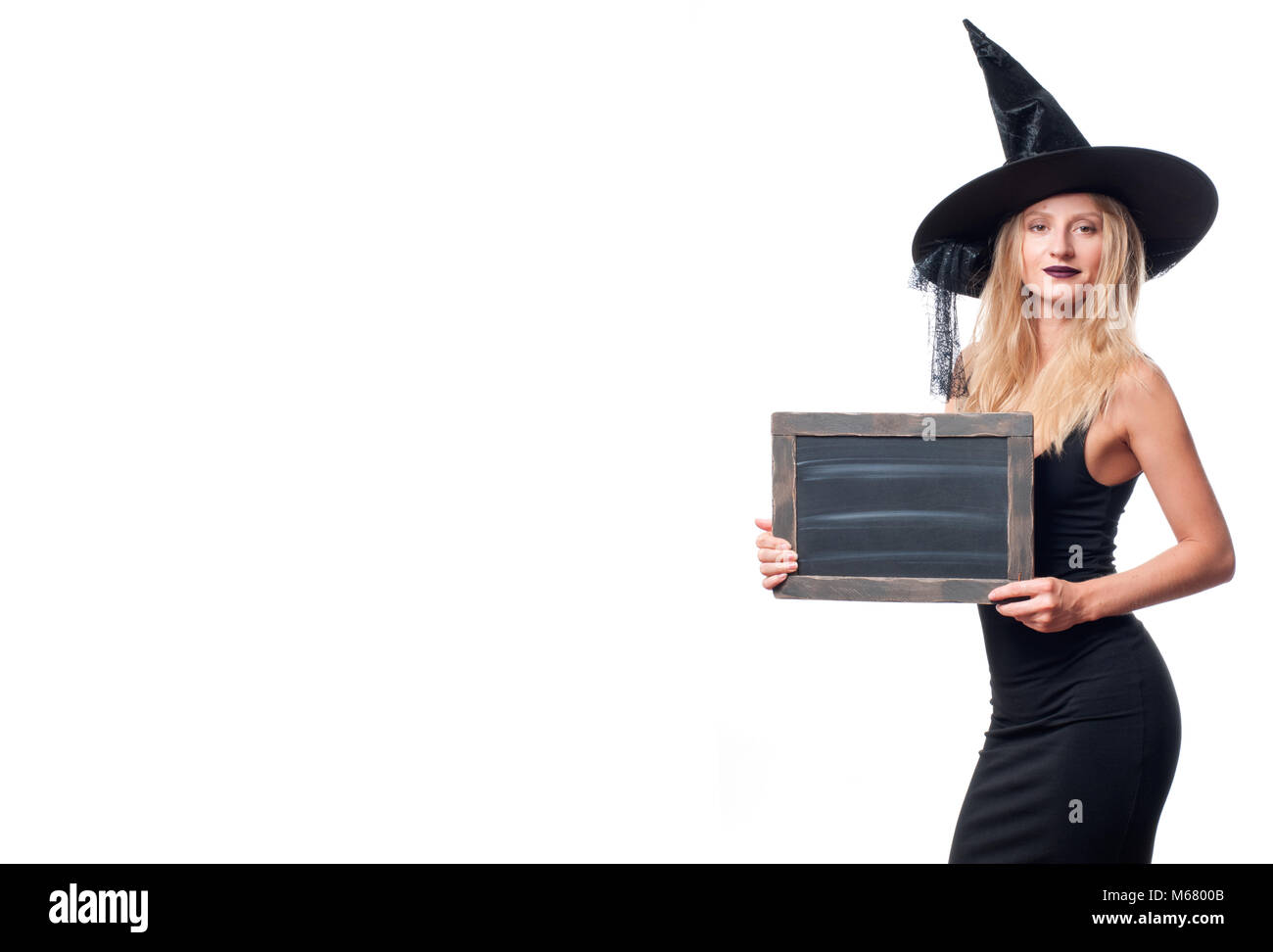 Happy woman in witch halloween costume with hat smiling on white background - Stock Image