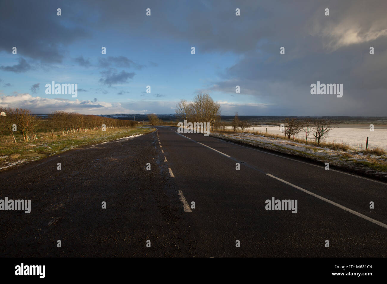 Road on top of Searby Hill with views around of snow on a partly overcast day in North Lincolnshire, UK - Stock Image