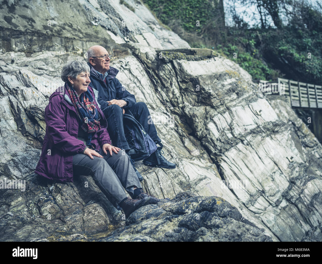 A senior couple is sitting on the rocks by the sea - Stock Image