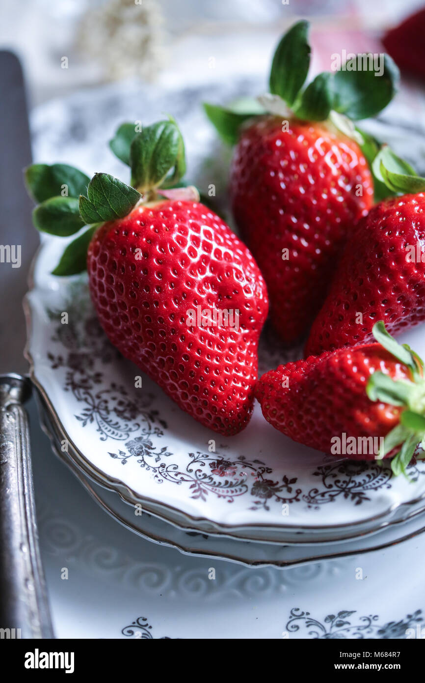 Fresh raw strawberries on a white plate - Stock Image