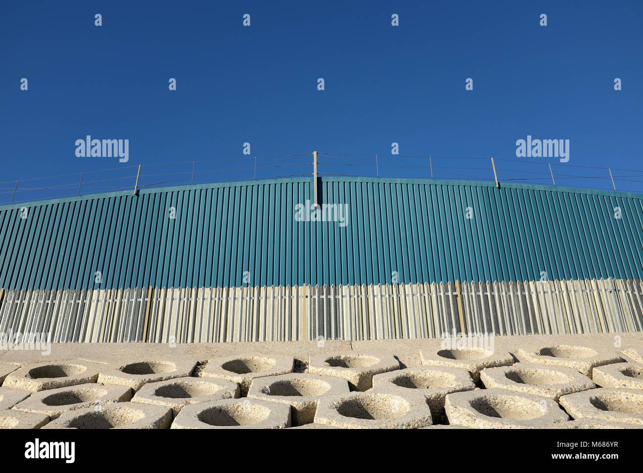 Shoreham Port, West Sussex, England. Sea defences and bulk storage shed, Southwick Beach. Stock Photo