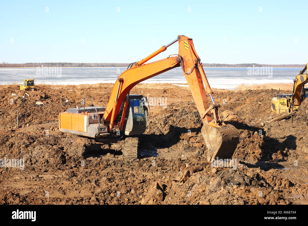 Construction of moorings for the parking of boats - Excavators work in dirt - Stock Image