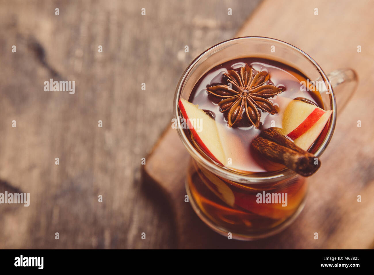 hot spicy beverage. Hot drink (apple tea, punch) with cinnamon stick and star anise. Seasonal mulled drink. - Stock Image