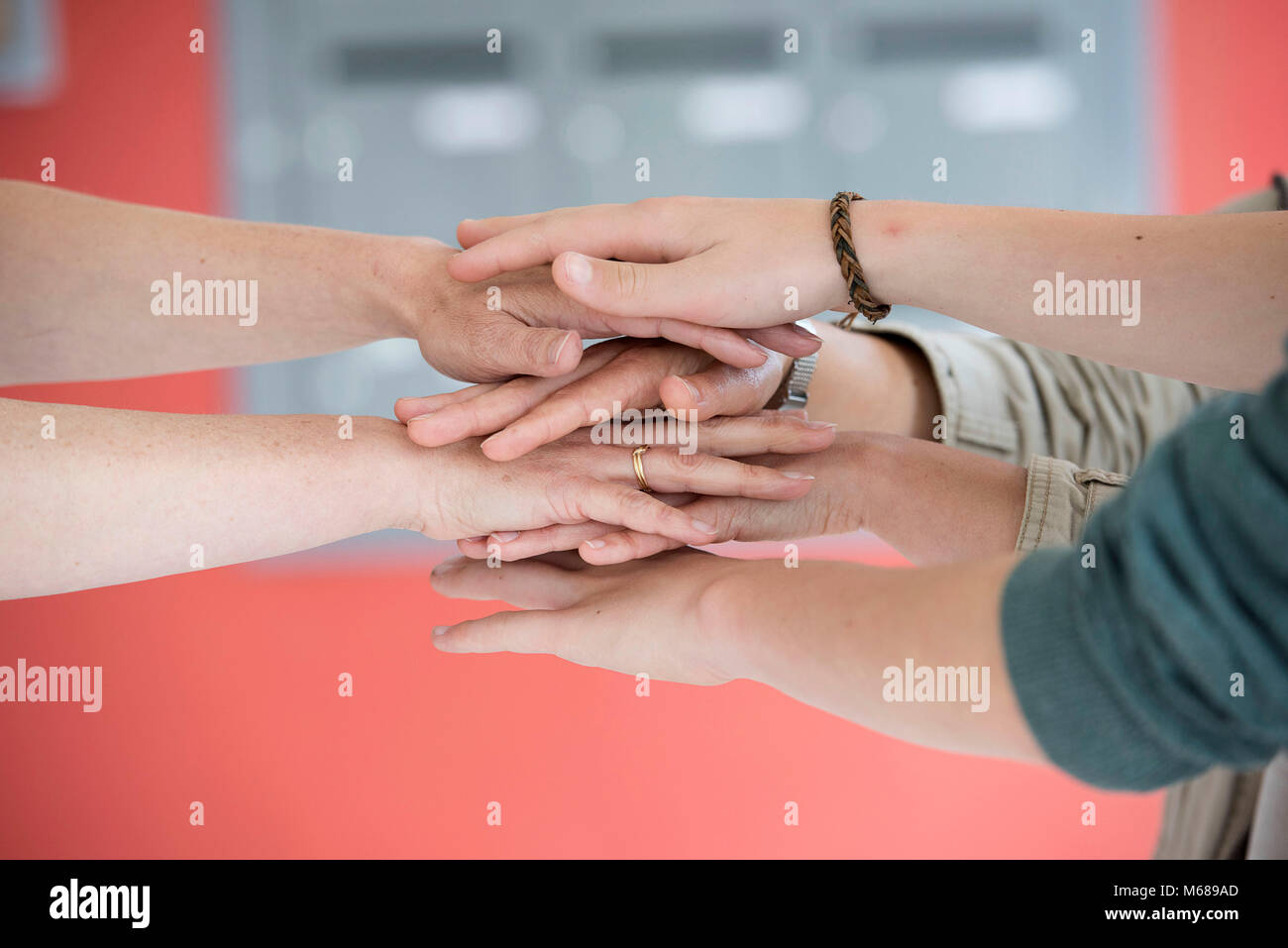 Hands of several persons lying on top of each other - Stock Image