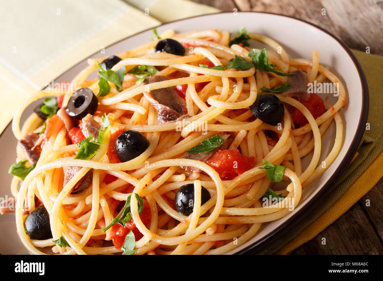 Italian food: spaghetti alla putanesca with anchovies, tomatoes, garlic, black olives and greens close-up on a plate. - Stock Image