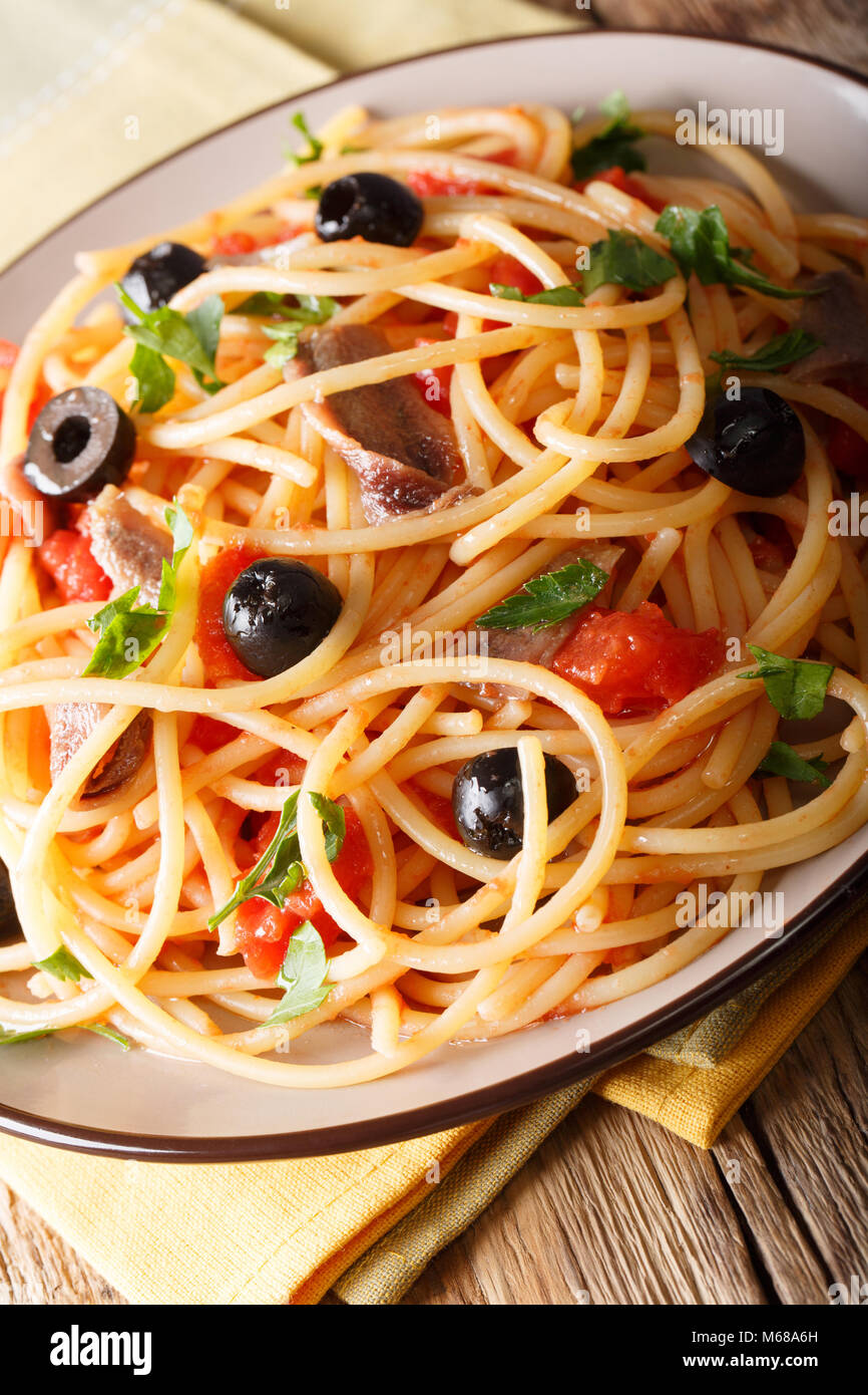 Italian pasta Alla Puttanesca with anchovies, tomatoes, garlic and black olives macro on a plate. vertical Stock Photo