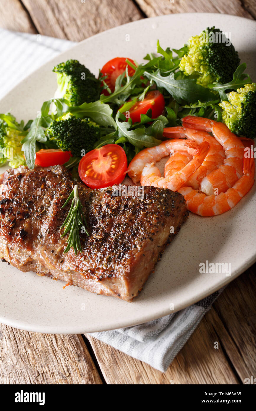 Delicious juicy barbequed steak and prawns with vegetable salad closeup on the plate. Surf and Turf style. Vertical - Stock Image