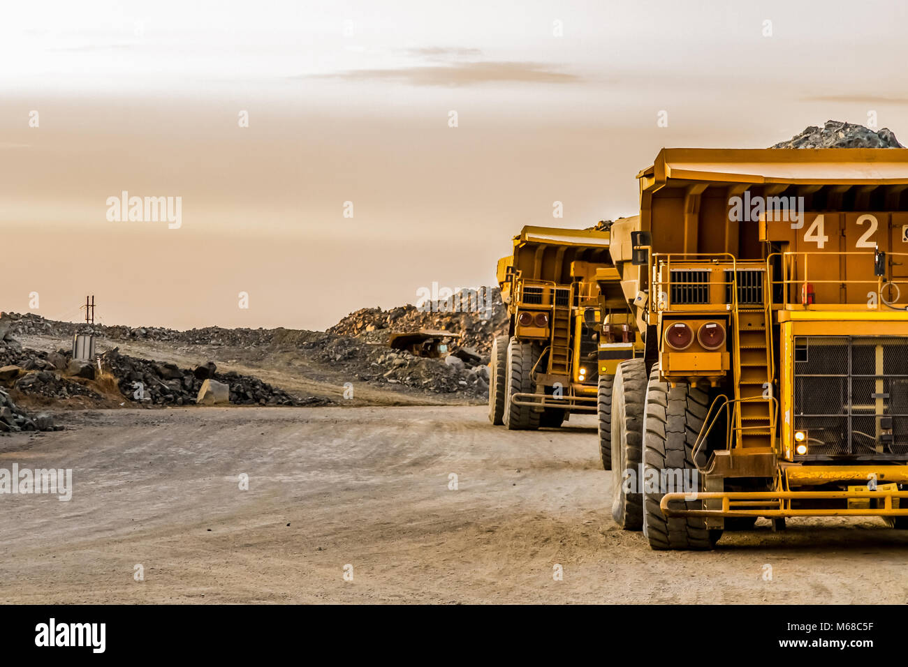 Large Dump Trucks transporting Platinum ore for processing - Stock Image