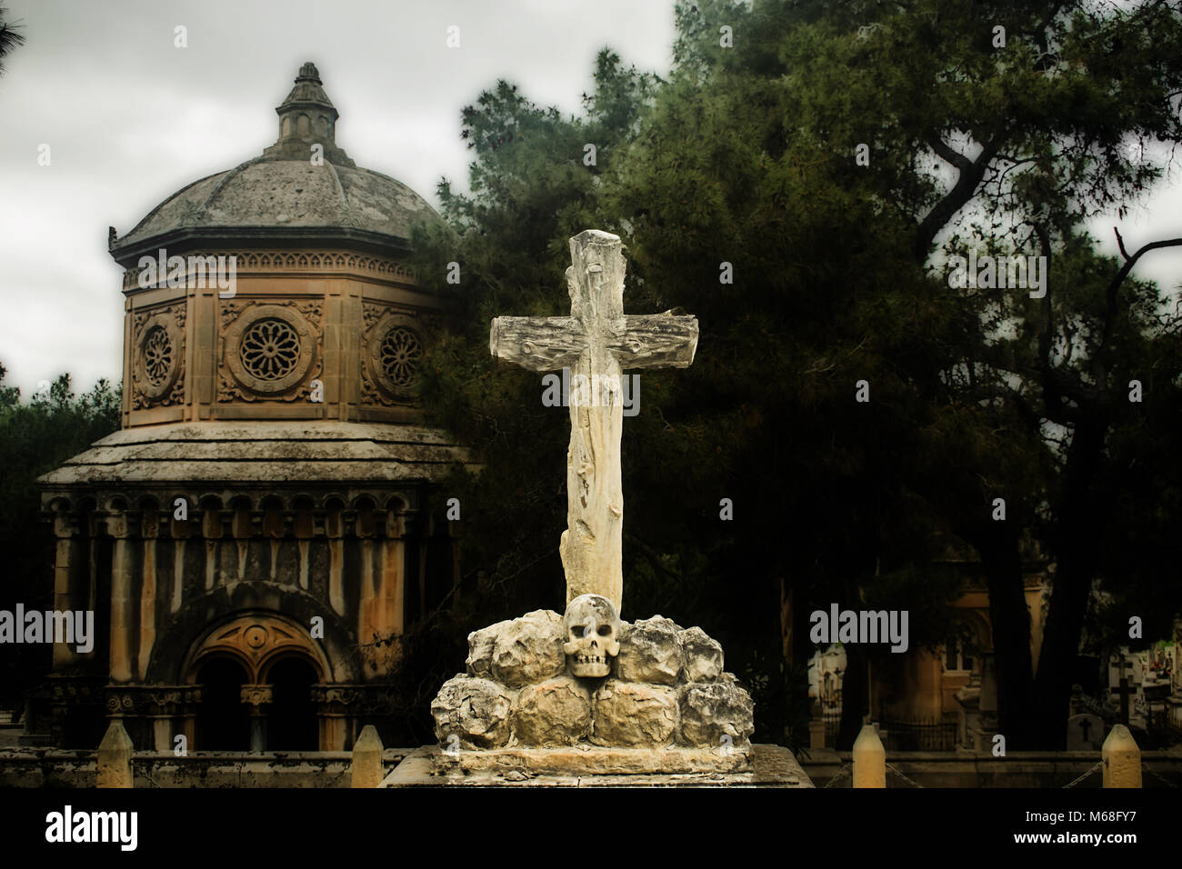 A wooden cross built on a skull with a cemetry in the background. Stock Photo