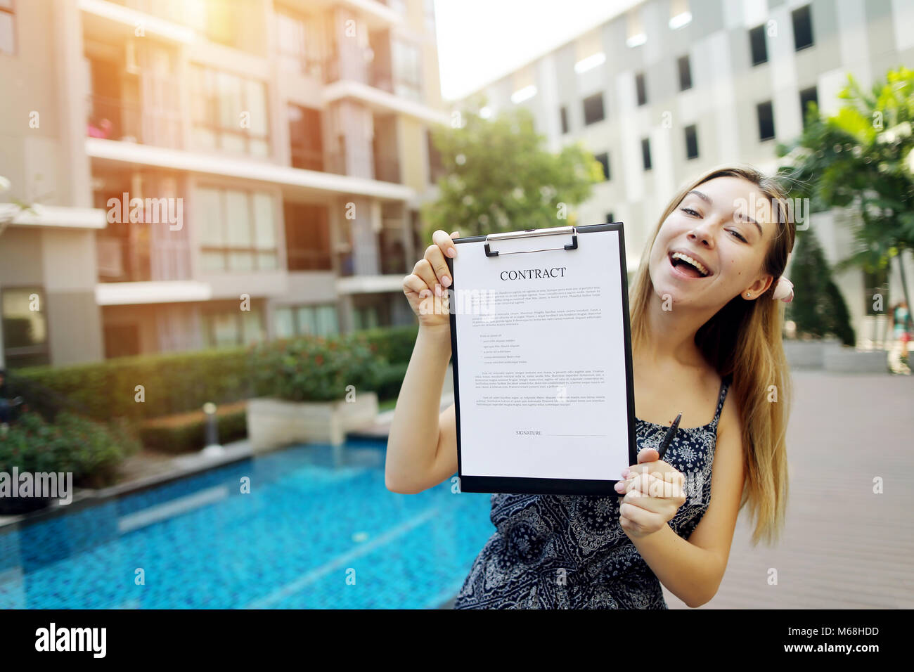 young girl proposes to sign contract to live in warm countries beautiful girl on background of pool suggests signing Stock Photo
