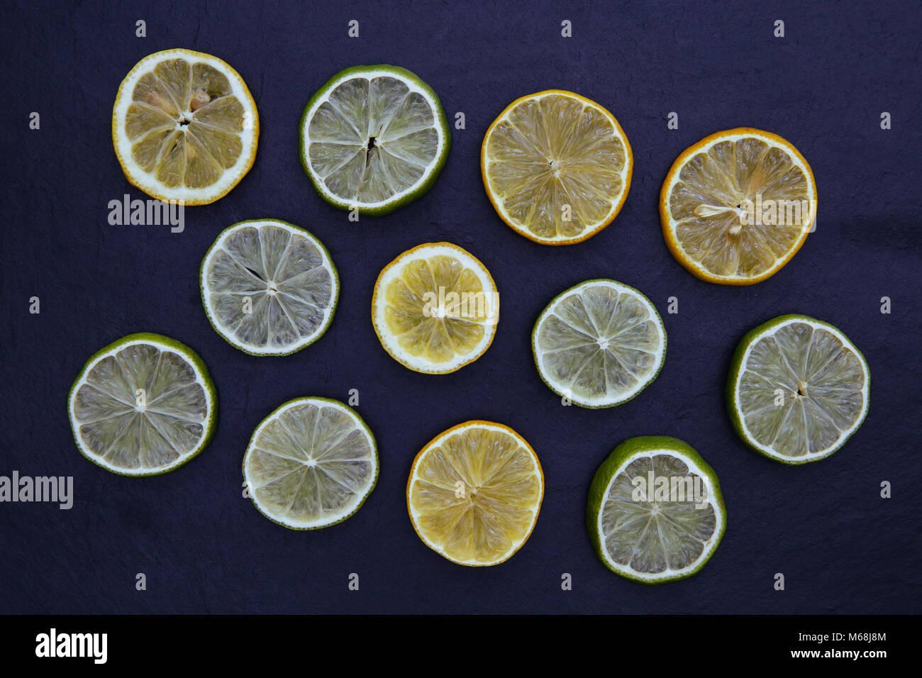 Lemon lime slices food on dark background - Stock Image