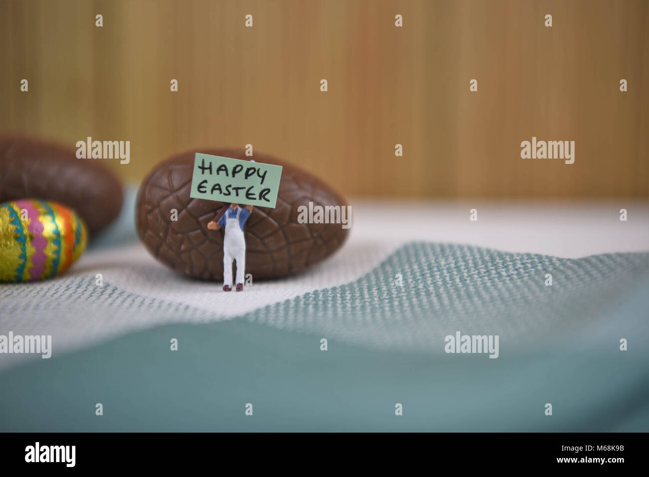 happy Easter words with chocolate Easter eggs and cute miniature person figurine Stock Photo