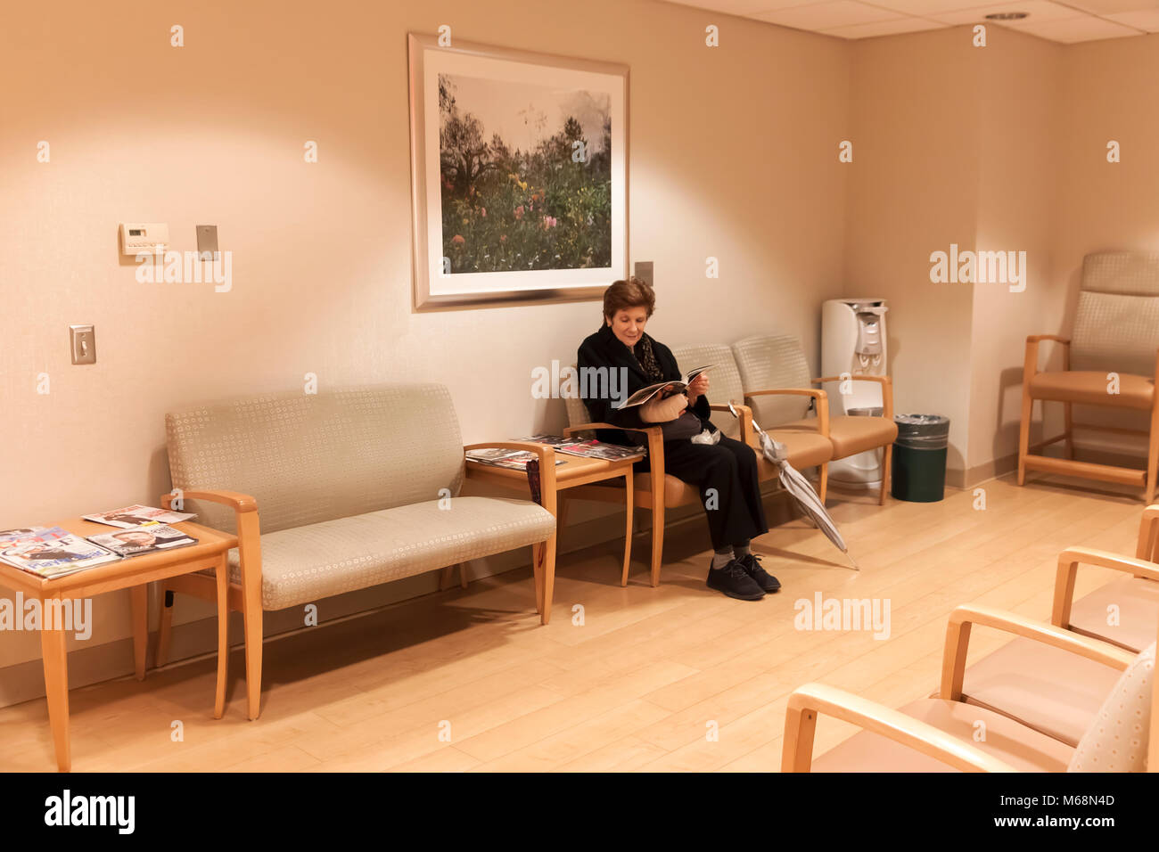 Female sitting in the waiting room of a doctor's office. - Stock Image