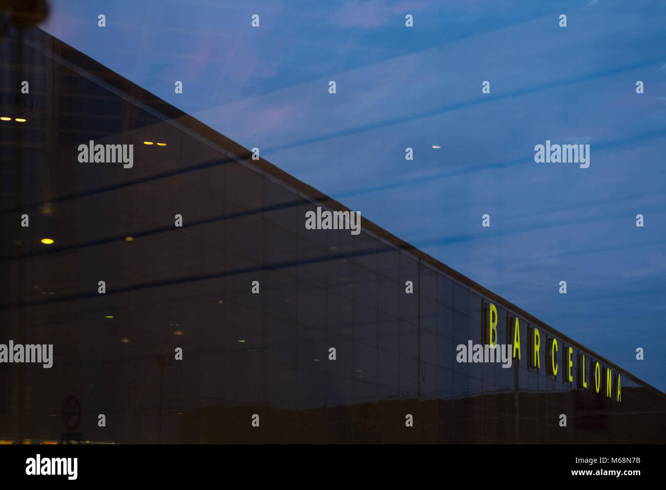 Glass facade as seen through another window of Barcelona Airport, the main airport of Catalonia, Spain. - Stock Image