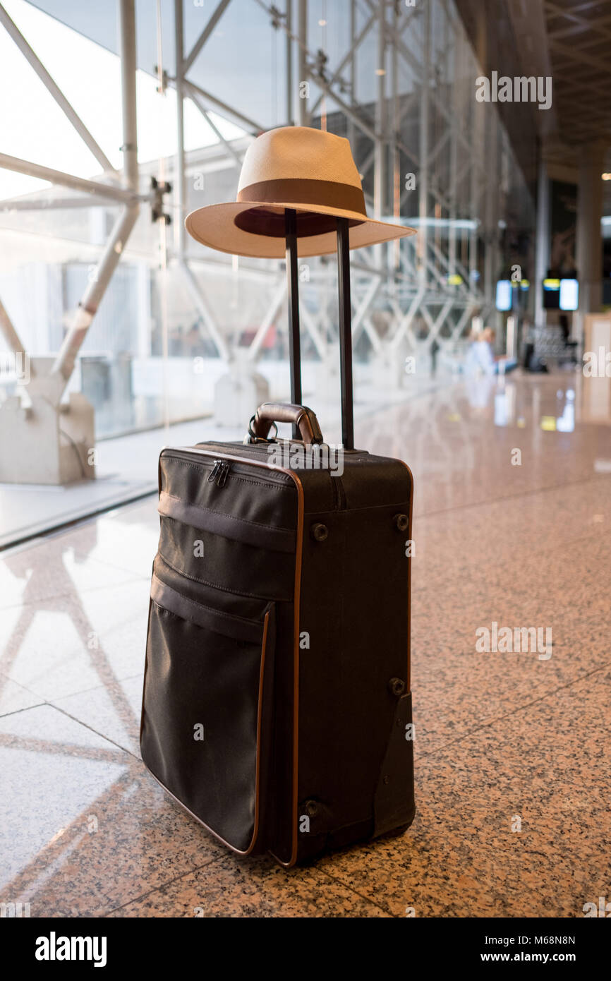 Elegant suitcase with summer hat at the airport. Travel and tourism concept. - Stock Image