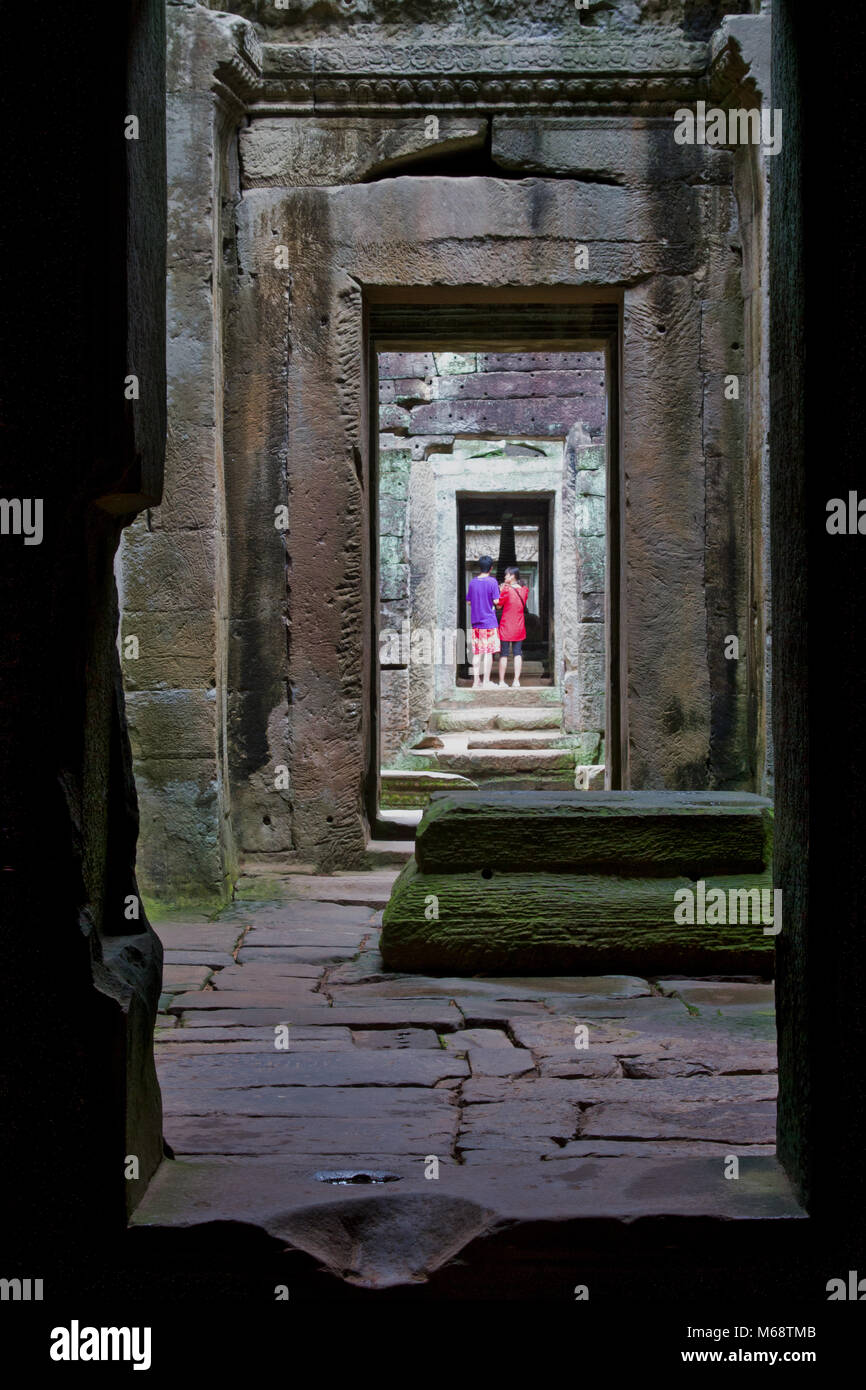 Visitors in doorway, exploring Angkor Wat, an UN World Heritage Site in Cambodia. - Stock Image