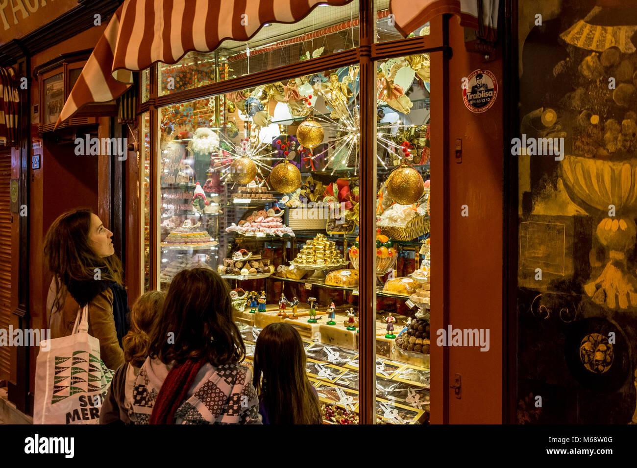 Auslage, Schaufenster eines Süßwarengeschäfts in Palma de Mallorca mit staunenden Passanten - Stock Image