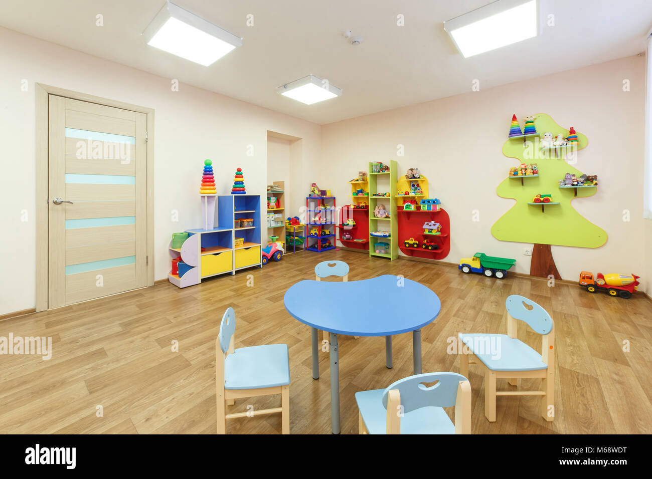 Blue table for classes with children and light pink colored game room with in the kindergarten - Stock Image