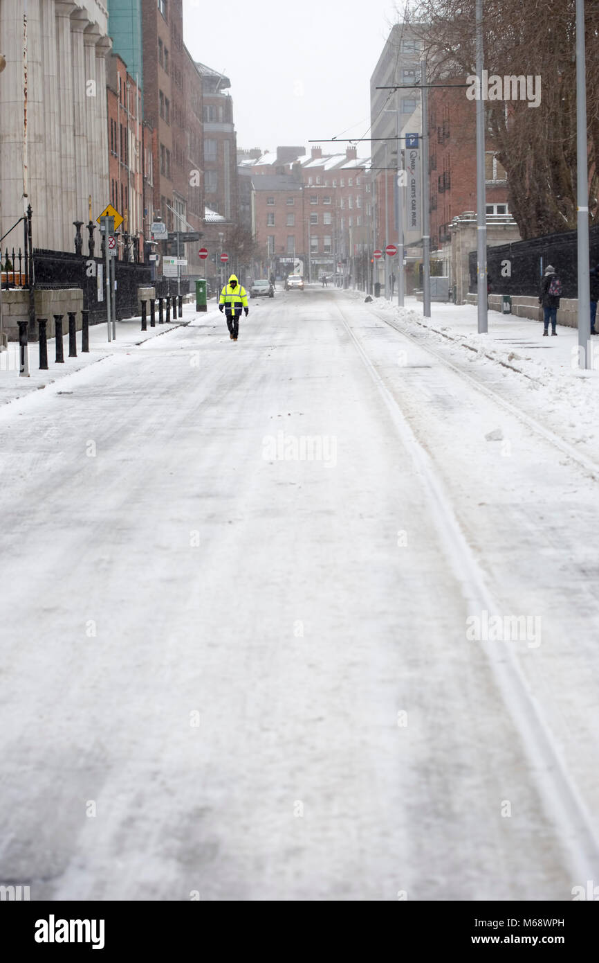 Man walking in city centre on street covered in snow. Dublin/Ireland. Beast from the East - Stock Image