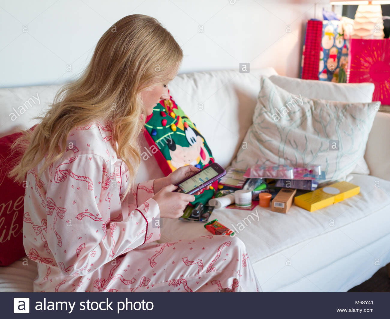 Young woman wearing pajamas sitting on couch looking at her IPhone on Christmas morning, USA - Stock Image
