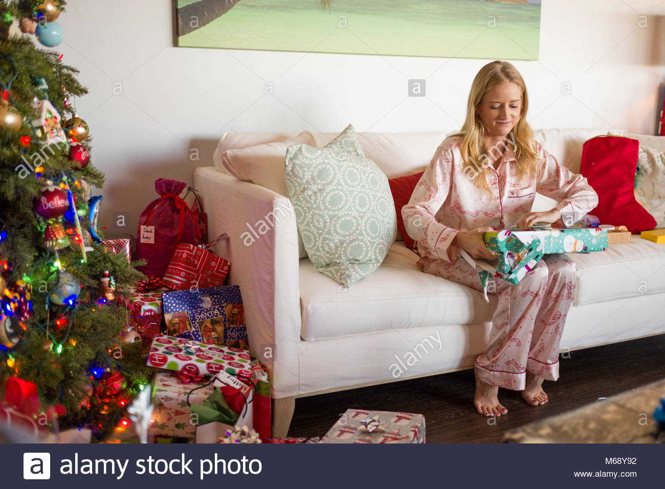 Young woman wearing pajamas sitting on couch opening gift wrapped Christmas present on Christmas morning, USA - Stock Image