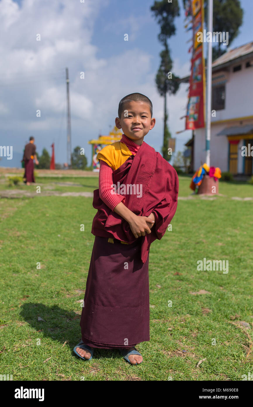 Pelling, India - April 26, 2017: Unidentified young novice buddhist monk in traditional red robes standing in front - Stock Image