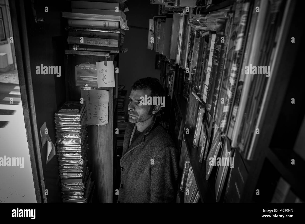 Simao Carneiro, owner of what is possibly the smallest bookshop in the world, in Lisbon, Portugal. - Stock Image