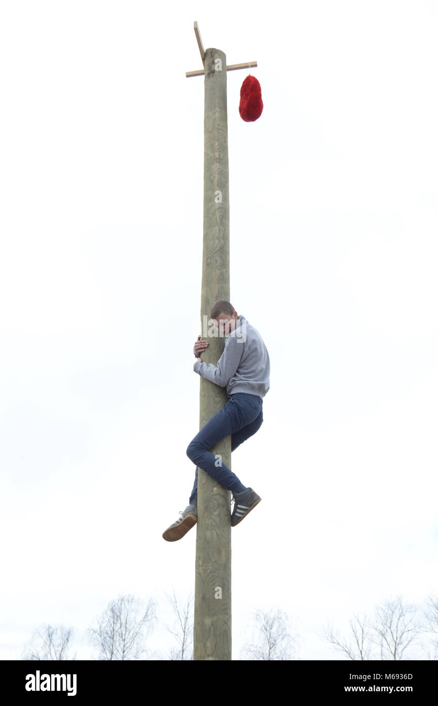 Kovrov, Russia. 13 March 2016. Shrovetide celebration. Holiday participant climbs onto a wooden pillar trying to - Stock Image