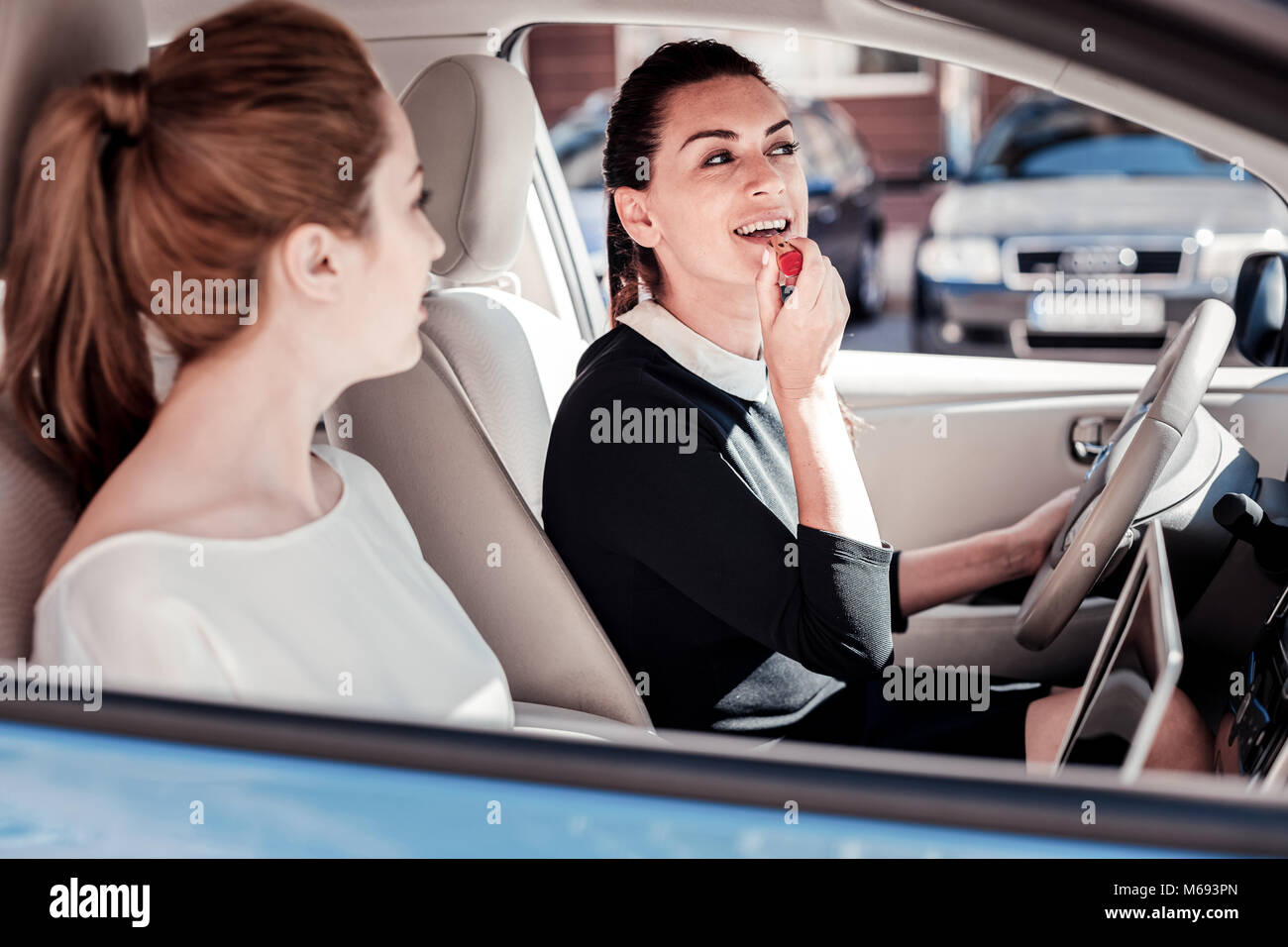 Stylish fashionable woman sitting in the car and sprucing. - Stock Image
