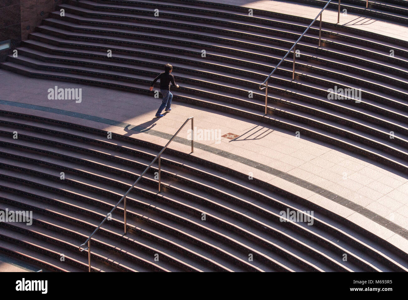 Shadows of a person on steps in the modern structure of Kyoto railway station that houses a department store and - Stock Image