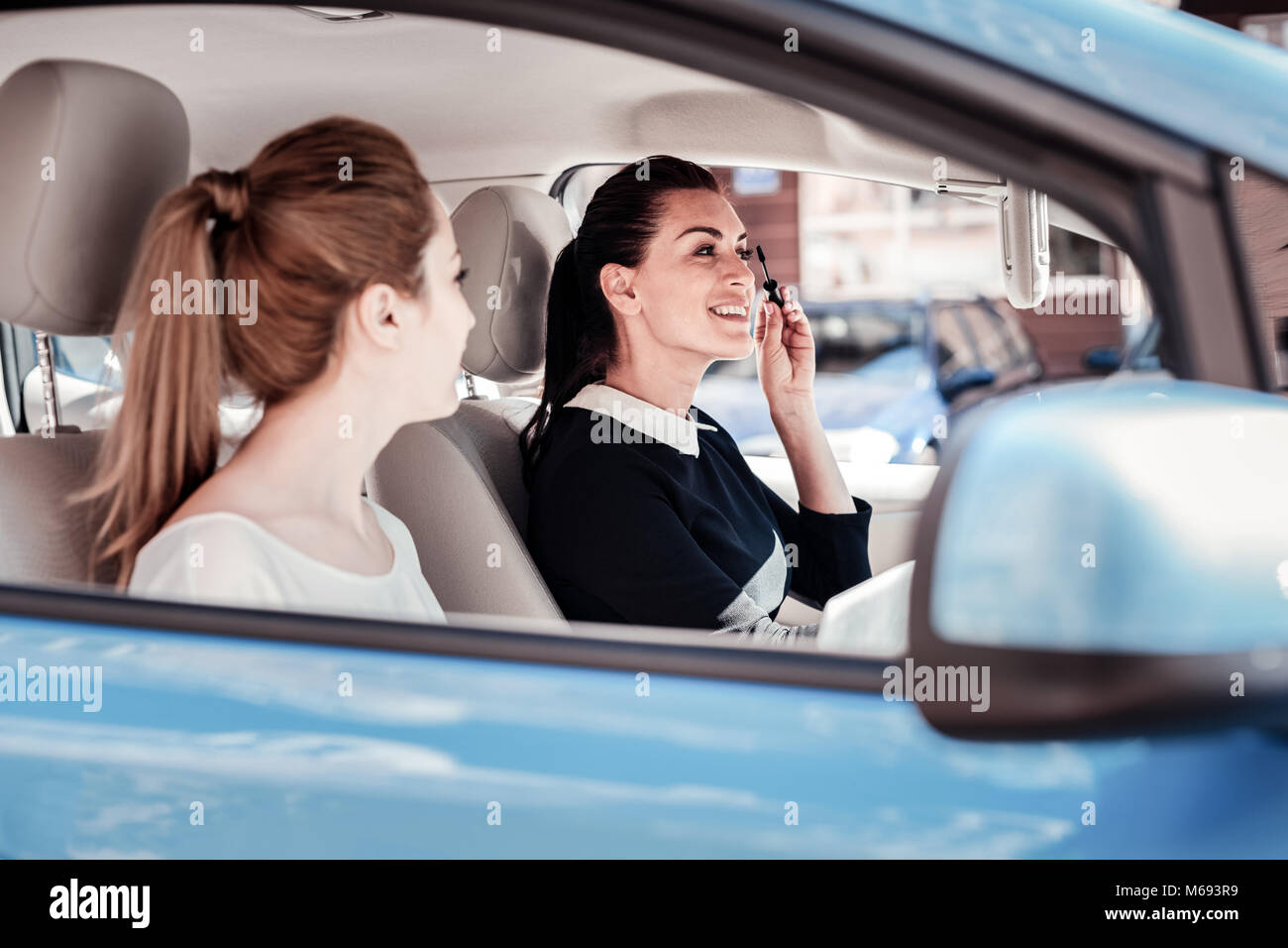 Fashionable satisfied woman sprucing and being in the mirror. Stock Photo