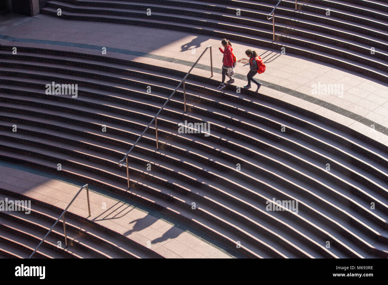 Shadows of people on steps in the modern structure of Kyoto railway station that houses a department store and huge - Stock Image